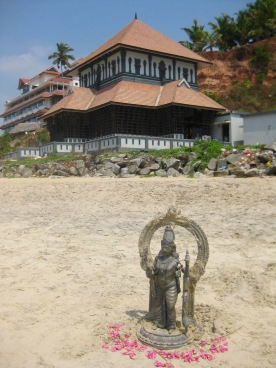 Hindu statue on beach in front of temple